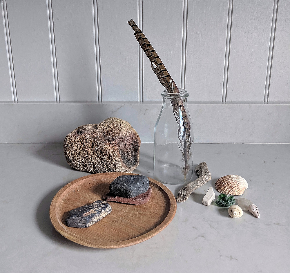 A collection of found natural objects: shells, seaglass, stones, feather. And a glass bottle-shaped vase and a wooden plate.