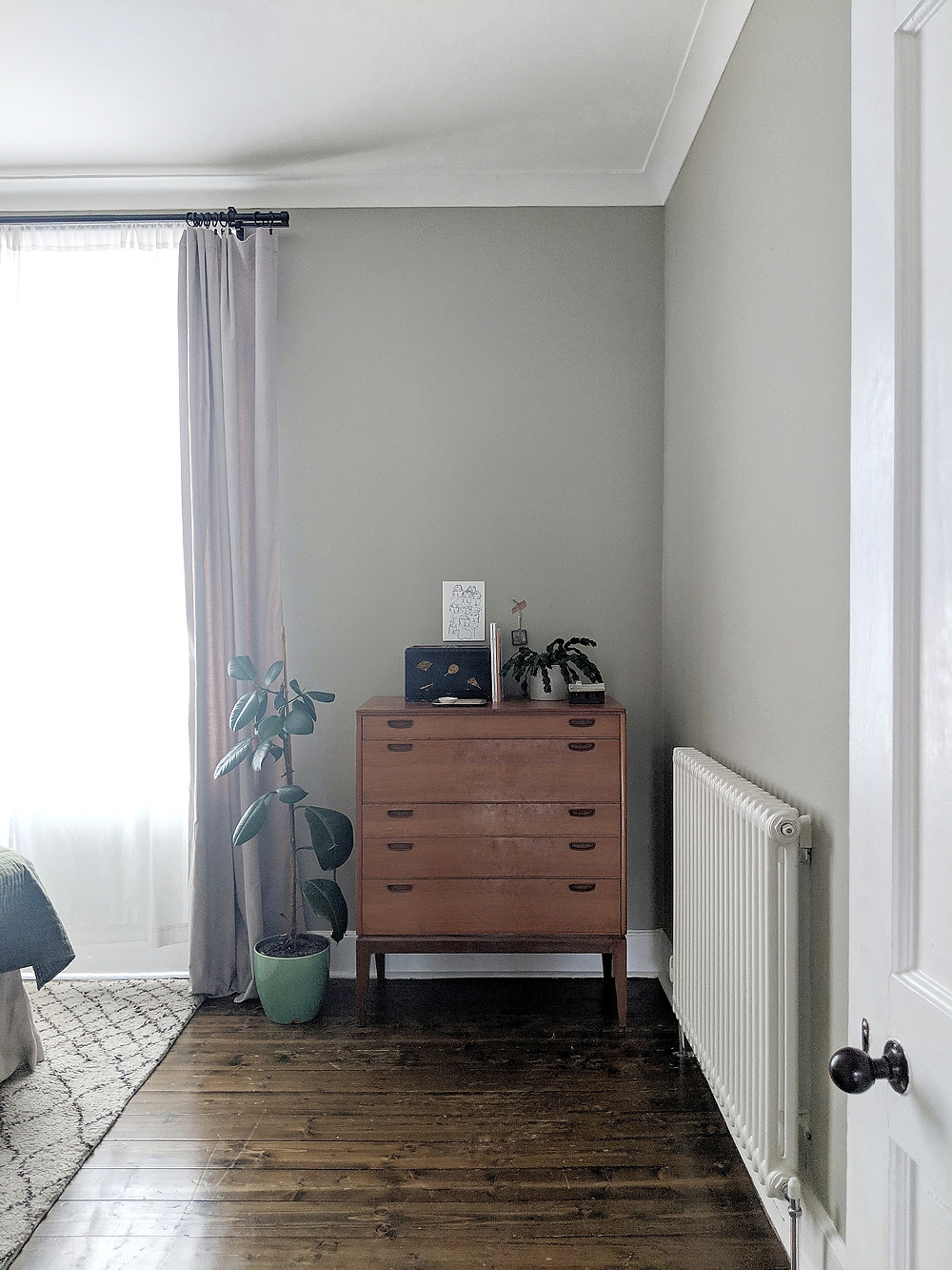 Mid-century chest of drawers with plants. Soft green walls, vintage=-style radiator, dark wooden floors.