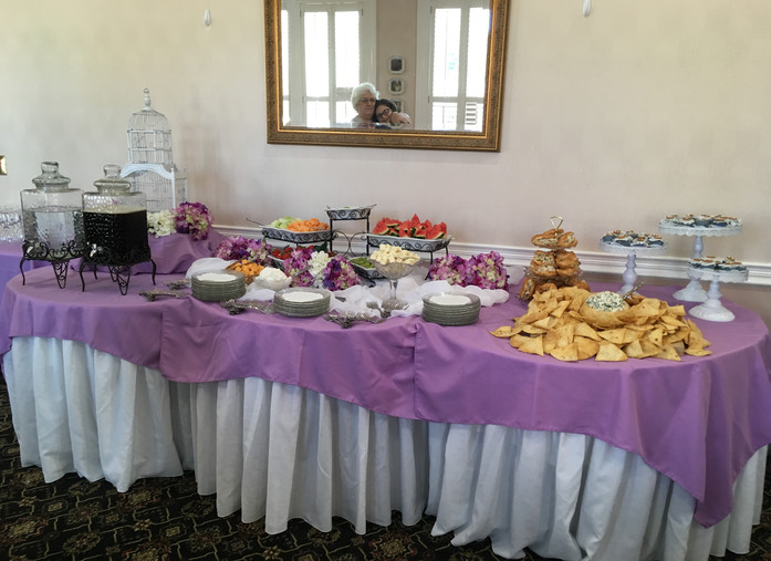A spread of fruit, chicken salad sandwiches, and dip.