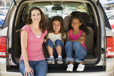 Woman with two young girls sitting in ba