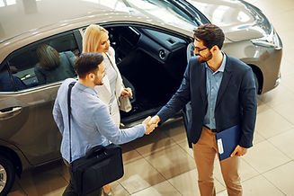 Young couple shaking hands with sales ag