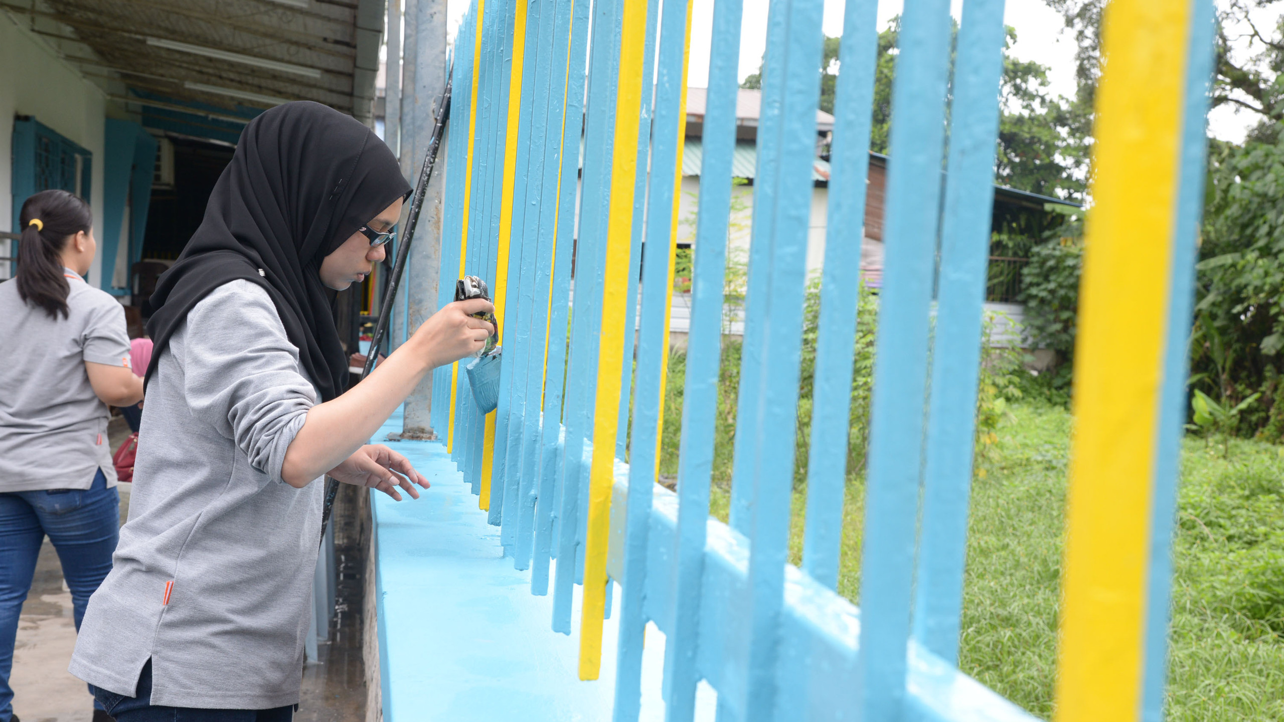 Guardian Malaysia employees volunteering their time to help in the improvement works of the charity home