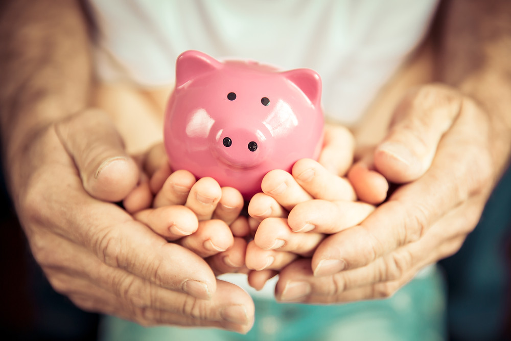Family hands holding a pink piggy bank