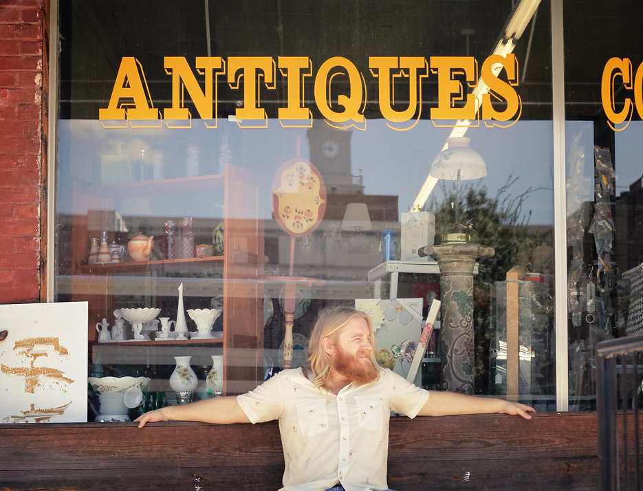 BJ Wilbanks, sitting in front of an antiques store