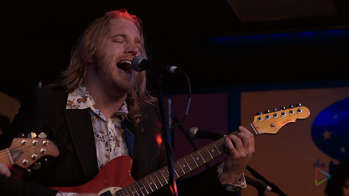 BJ Wilbanks sings into a microphone while playing electric guitar