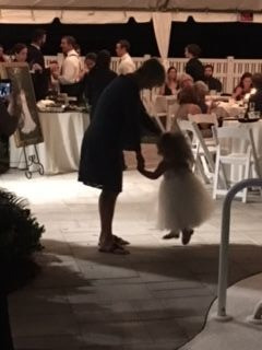 The mother of the bride shares a dance with the flower girl