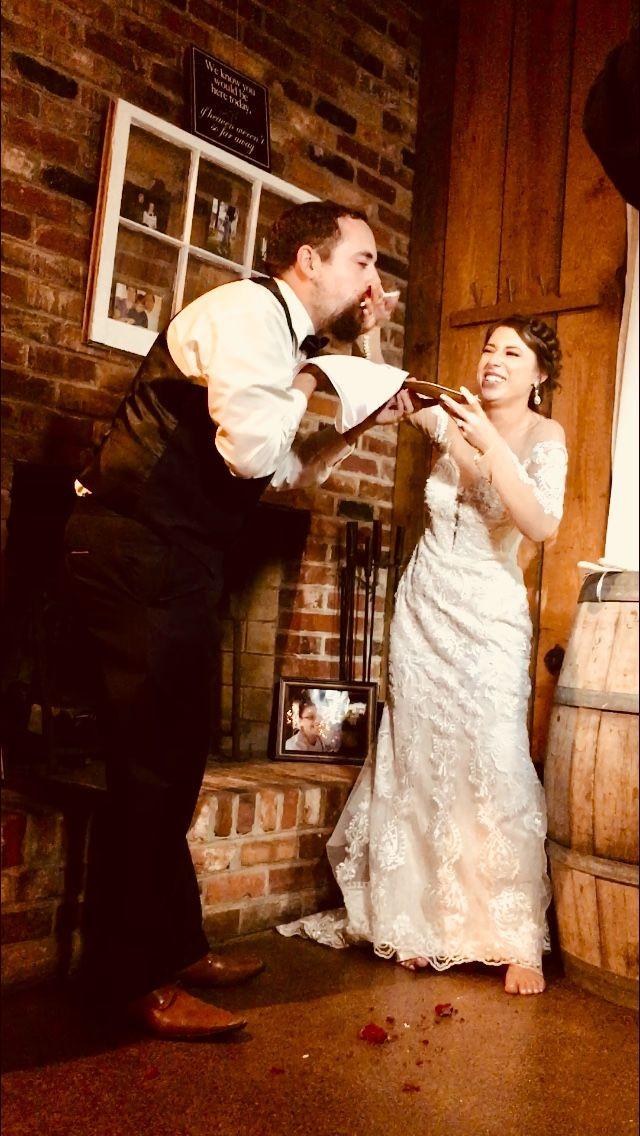 Bride smashing wedding cake in Grooms face