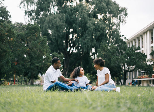 family-sitting-on-grass-near-building-11