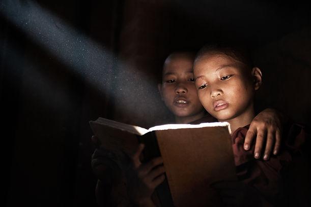 Little monks reading book inside monaste