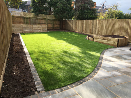 Artificial grass and sandstone paving