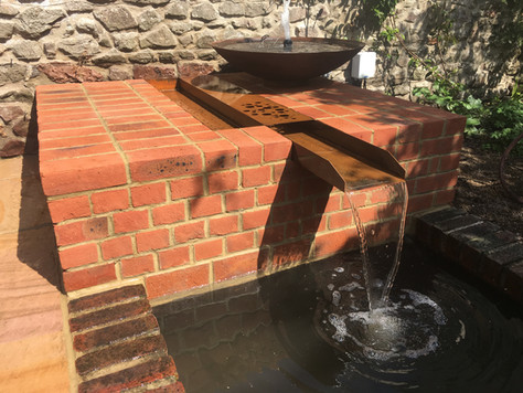 Beposke brick work and metal water bowl and cill.