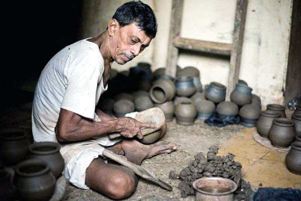 A Dalit potter at work producing candle holders for the shop