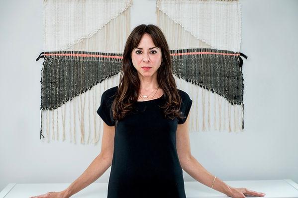 Artist Steffanie Goodman in front of diptych of woven art
