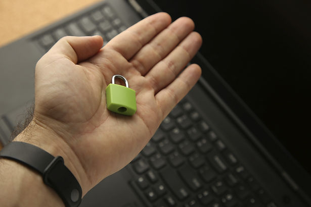 hand-holding-green-padlock-with-laptop-b