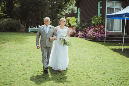 Campbell River Wedding Photographer at Haig Brown House Wedding Venue. The bride is walking down the isle