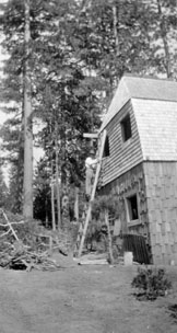M075 Man on ladder at Starkey cabin, cir