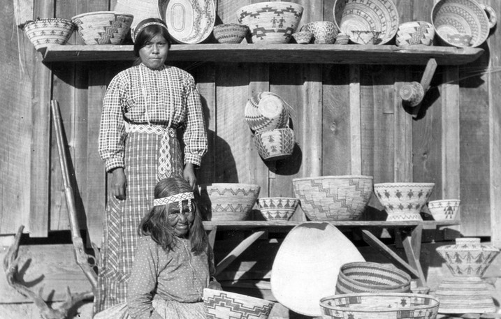 Dunlap Yokuts native Lizzie Chapa and one of her granddaughters display an array of handmade woven baskets. For the Yokuts of Central California, basket weaving was an essential part of life. Each carefully chosen design signified the region in which it was made as well as the purpose for which it would be utilized. Bob Adams