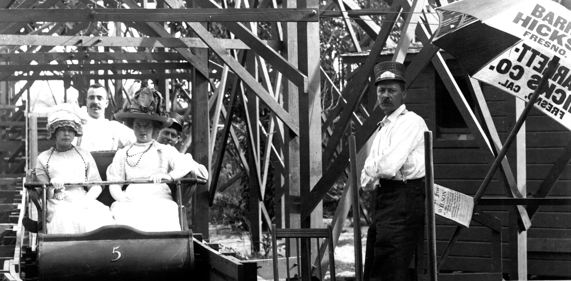 Zapp's Park RollerCoaster- Two park visitors risk their designer millinery aboard Car Number 5 while hurtling through afternoon skies on Zapp's rickety wooden roller coaster – circa 1911. Taken by Pop Laval.