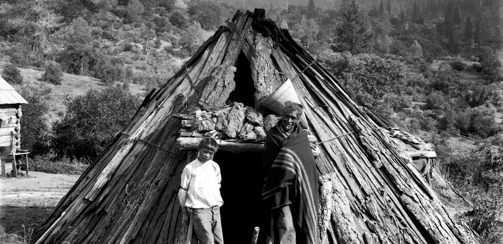 Monache man and boy in front of dwelling