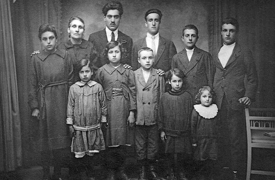 From the mid-1800s, many Italians were impoverished and jobs were scarce. The Della Maggioras from Porcari, Lucca were tenant farmers who placed hope in one son who was heading to America. They took a photo to send with him since he might not return. Shoes had to be borrowed from neighbors. Now the journey could begin…