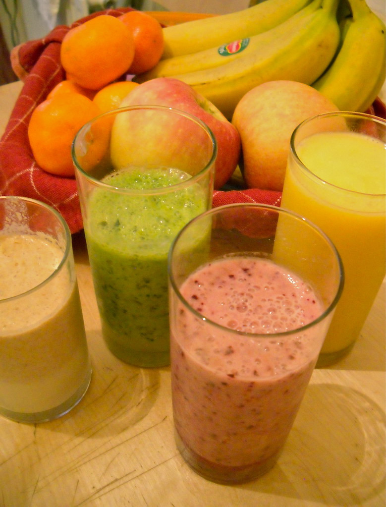 Pink and green smoothies stand in front of basket of bananas, tangerines and apples