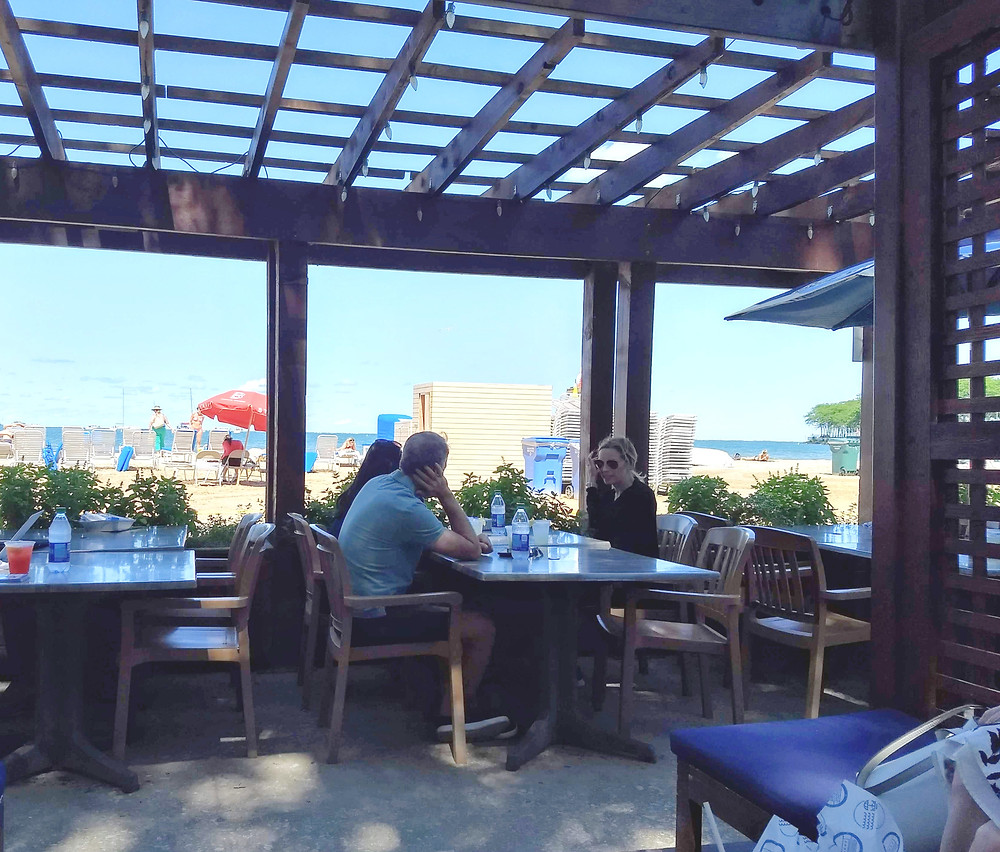 Under a wooden pergola, three adults dine at a table with a sunny Lake Michigan beach in the background