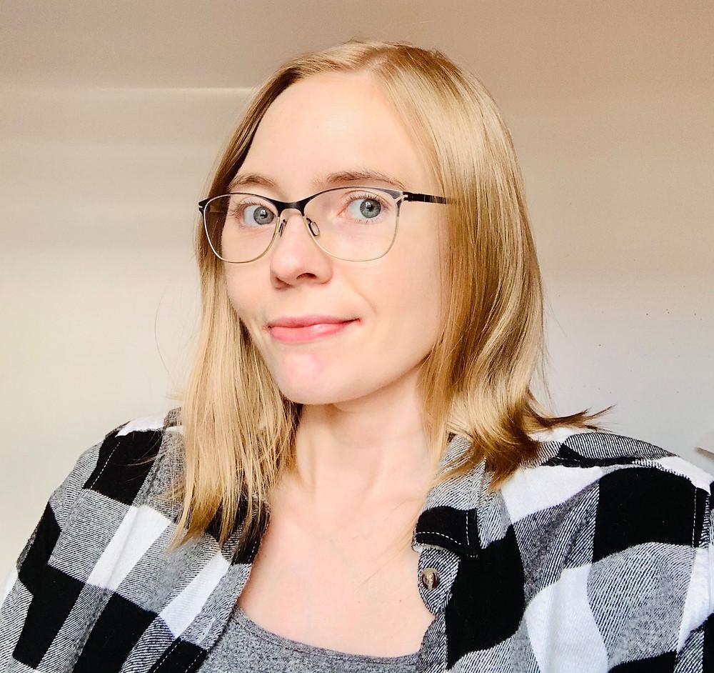 Andlitsmynd af Jönu Birtu Björnsdóttur. Hún er ljóshærð, með gleraugu og í köflóttri svarthvítri skyrtu.