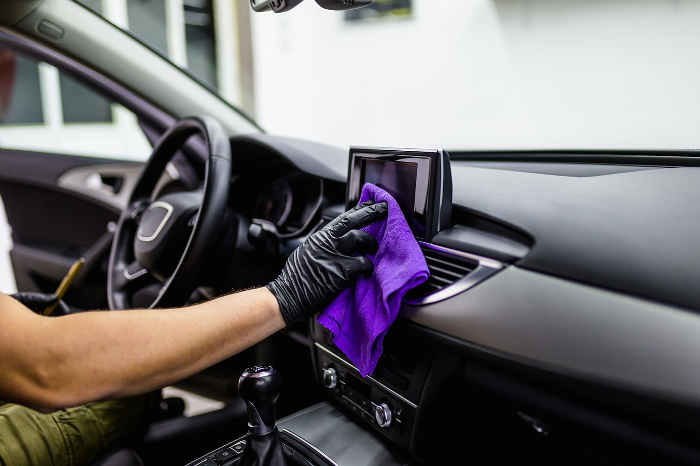 A man cleaning car interior, car detailing (or valeting) concept. Selective focus. .jpg