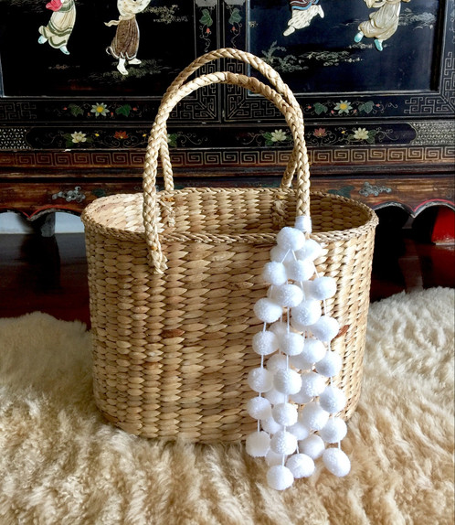 A Simply Chic Straw Basket Tote Bag With Unlined Interior And The Decorated Beautiful Long White Pom Poms