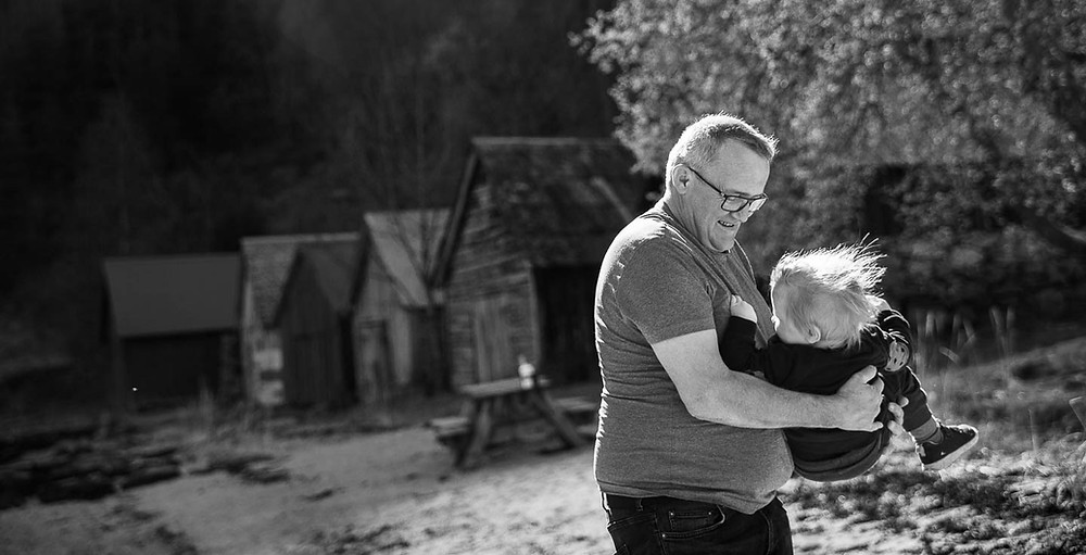 Bestefar leker med barnebarn, naturlige familiebilder