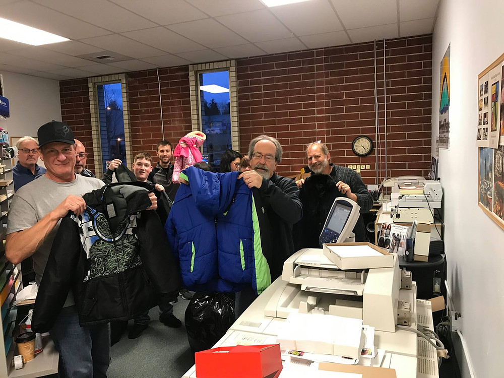 Community members holding up donated jackets.