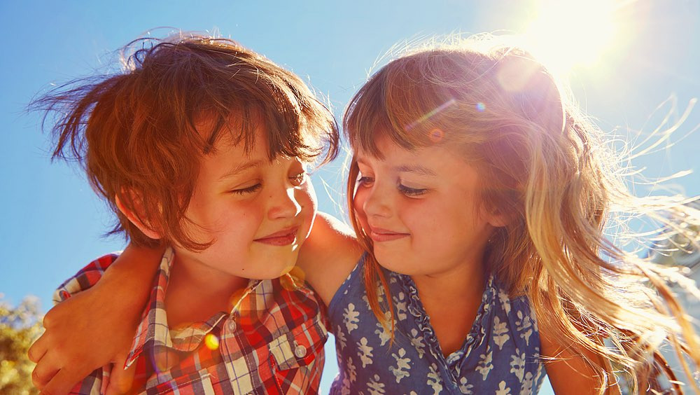Little boy and girl hugging outside in the sun