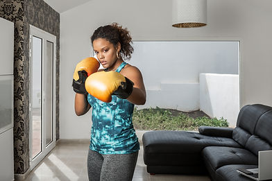 concentrated-african-american-sportswoman-activewear-boxing-gloves-doing-punches-while-tra
