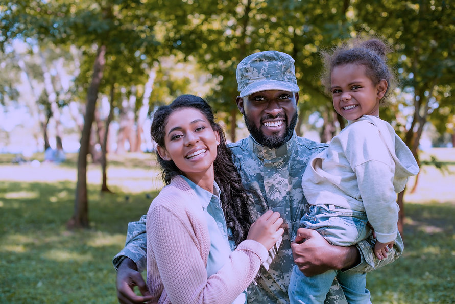 Military Wife, Military Man in Camo, their child. All are smiling and happy.