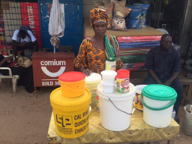 Milk vendor at local outdoor market in The Gambia during the rainy season in 2016. Photo by J. Washabaugh