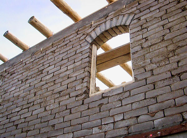 compressed earth block wall with an arch and vigas