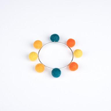 Orange, amber, yellow & teal pom pom & silver bangle