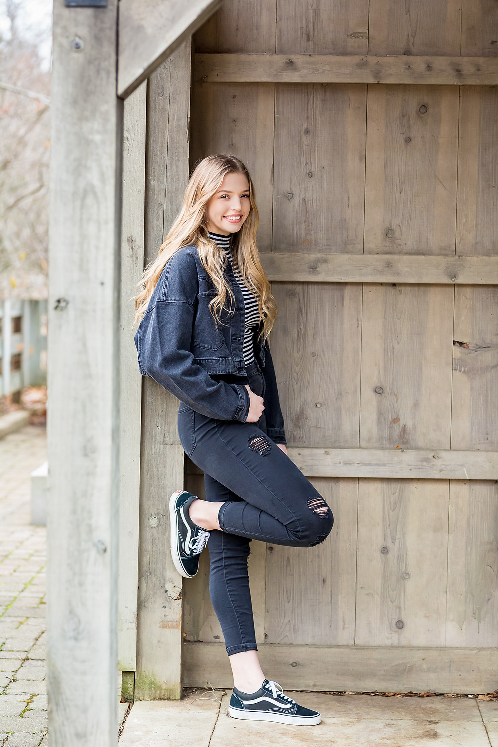 Genuine smile senior girl standing against wood wall with leg up ripped jeans denim jacket in unique pose senior session near Columbus Oh