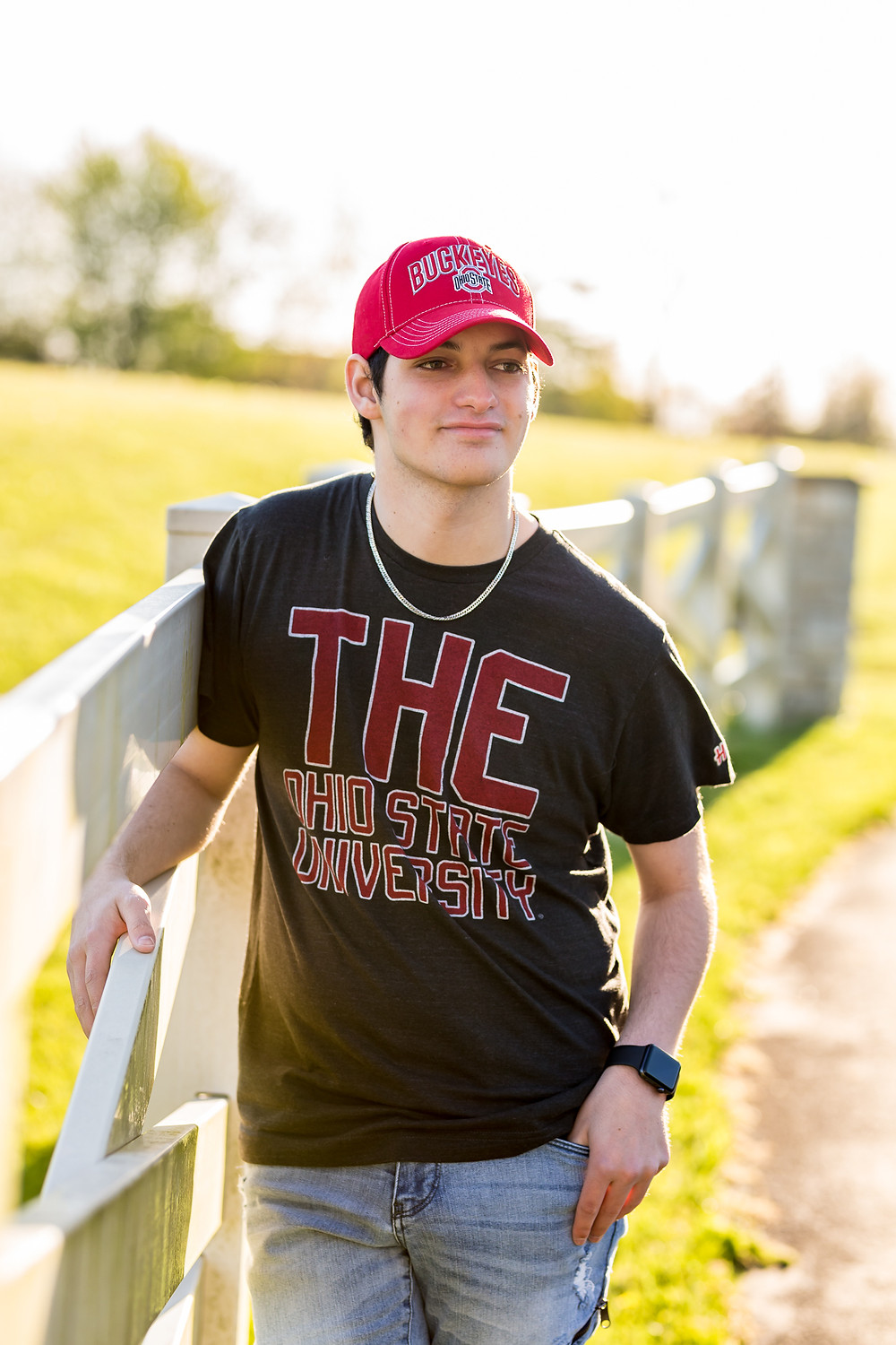 Senior guy in Westerville, Ohio wearing a Ohio State University T-shirt and hat for his Summer senior session holding onto a fence and looking away