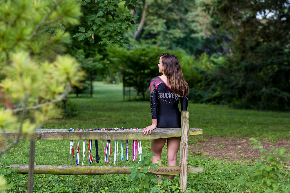 Unique custom senior portrait of teen gymnast girl in a Buckeye Gymnastics leotard leaning on fence away from camera with competitive gymnastics metals displayed