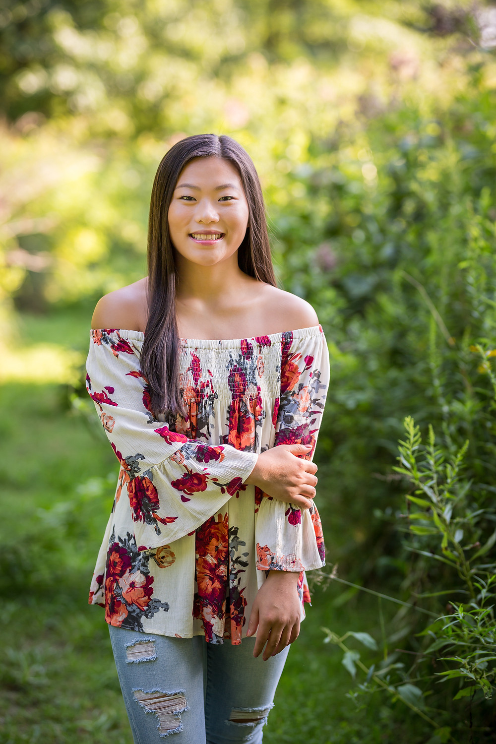 Senior girl smiles at camera wearing jeans and floral shirt during professional portrait session at Inniswood Metro Garden in Westerville Ohio standing near field