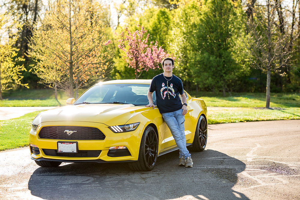 Westerville, Ohio high school senior leans against yellow sports car for senior portraits with colorful trees in the park