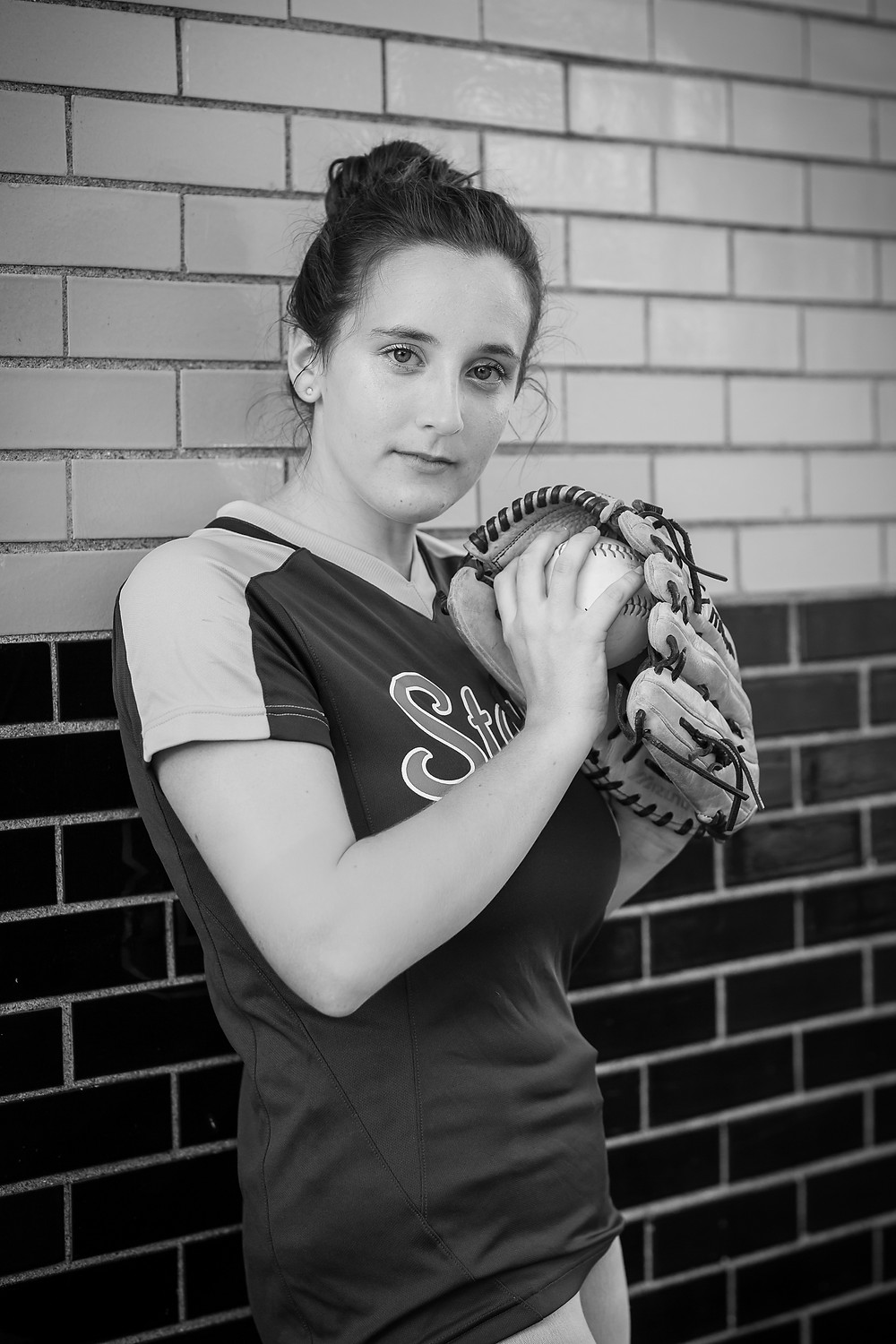 Black and white photo of senior girl in Uptown Westerville near Columbus, Ohio holding softball glove and ball and looking serious at camera for professional portraits