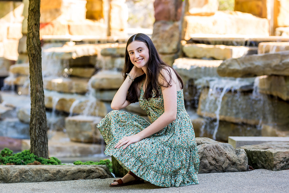 Westerville Senior Portrait of Reynoldsburg student in Gahanna Ohio by waterfall wearing a green dress and kneeling and smiling