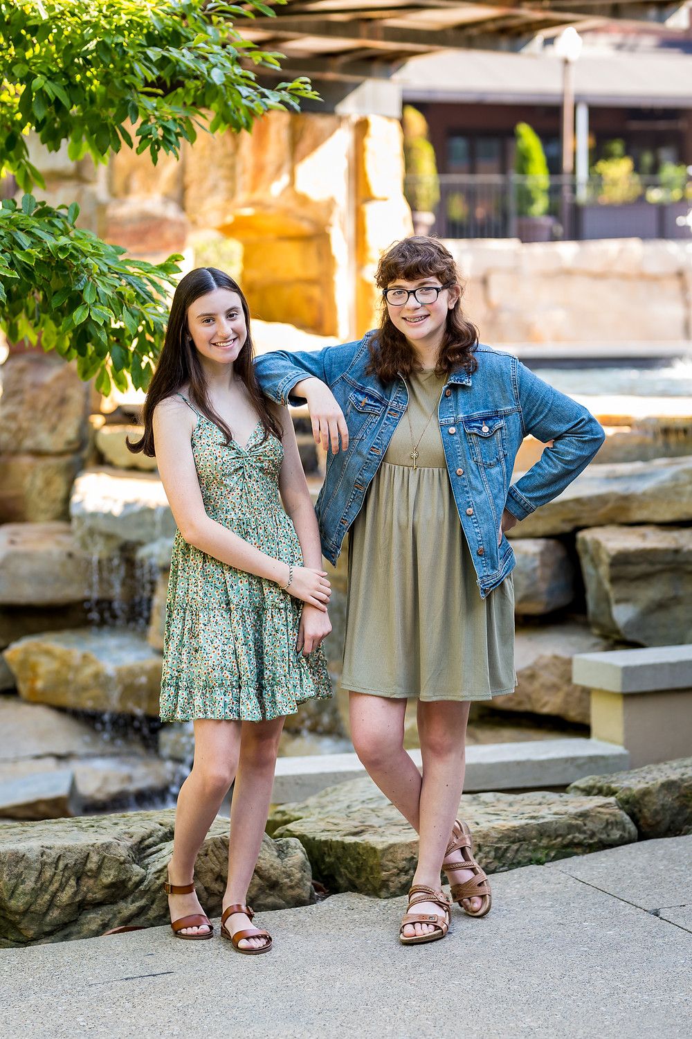 Teen sisters standing and leaning on each other both wearing green dresses and one in a denim jacket as photographed by Westerville Senior Photography in Gahanna, Ohio