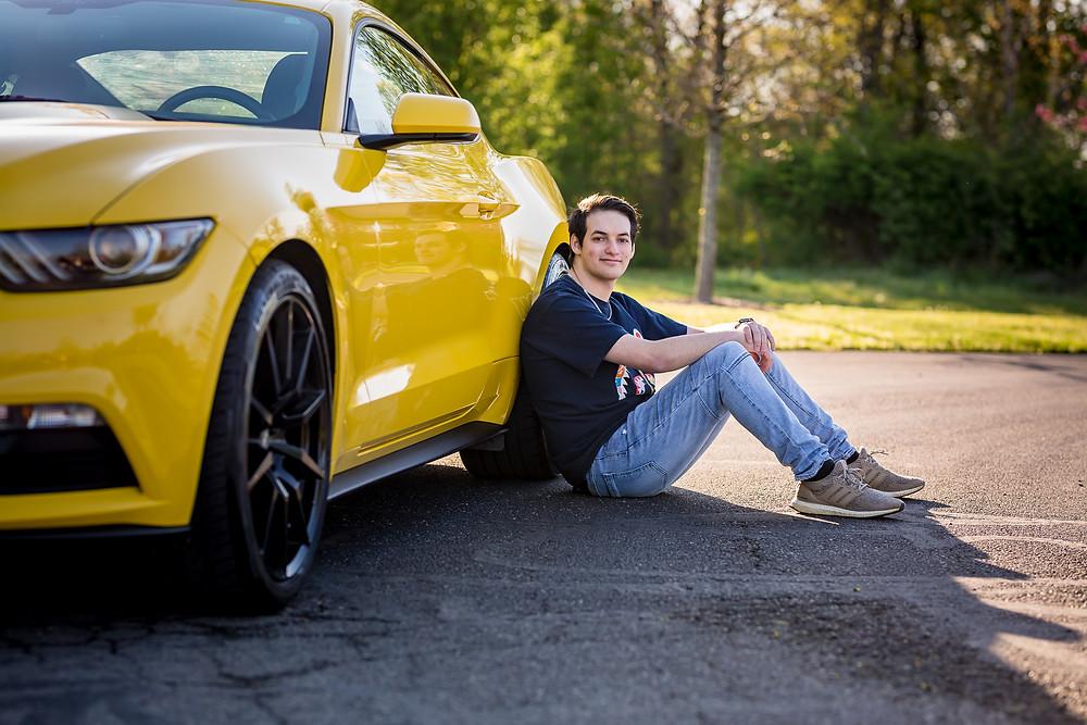 Custom senior portrait of teen near Columbus, Ohio wearing jeans and T-shirt sitting against yellow Mustang