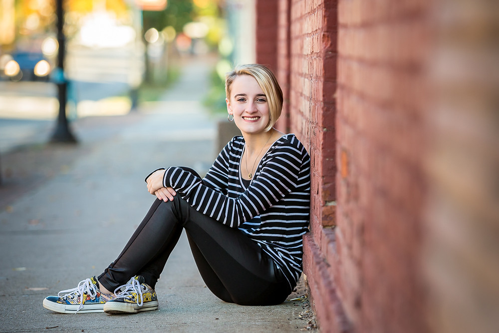 Westerville South High School senior sits by brick in uptown Westerville for senior photos