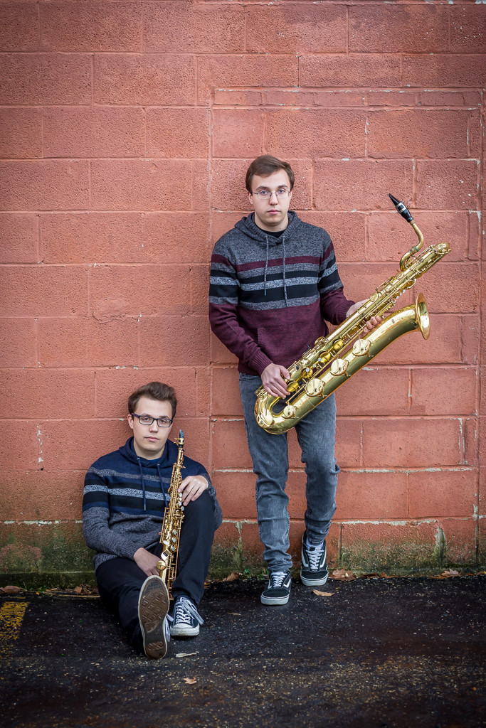 twin boys at senior session in Uptown Westerville against brick wall with instruments