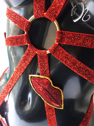 Detail close up of a gold ring, red glitter elastic and lip applique detail