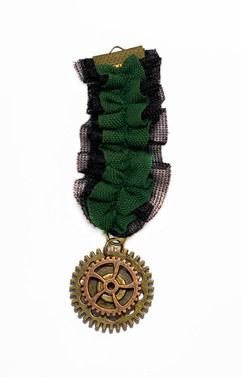 Green and black ruffled medal wirh a cog pendant